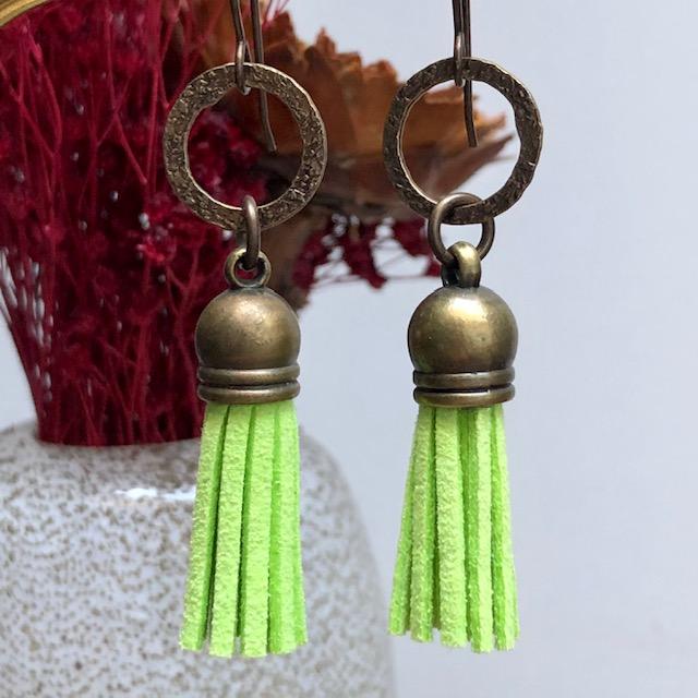 Boucles d'oreilles composées de pompons en suédine vert anis et d'anneaux en laiton. Crochets d'oreilles en laiton.