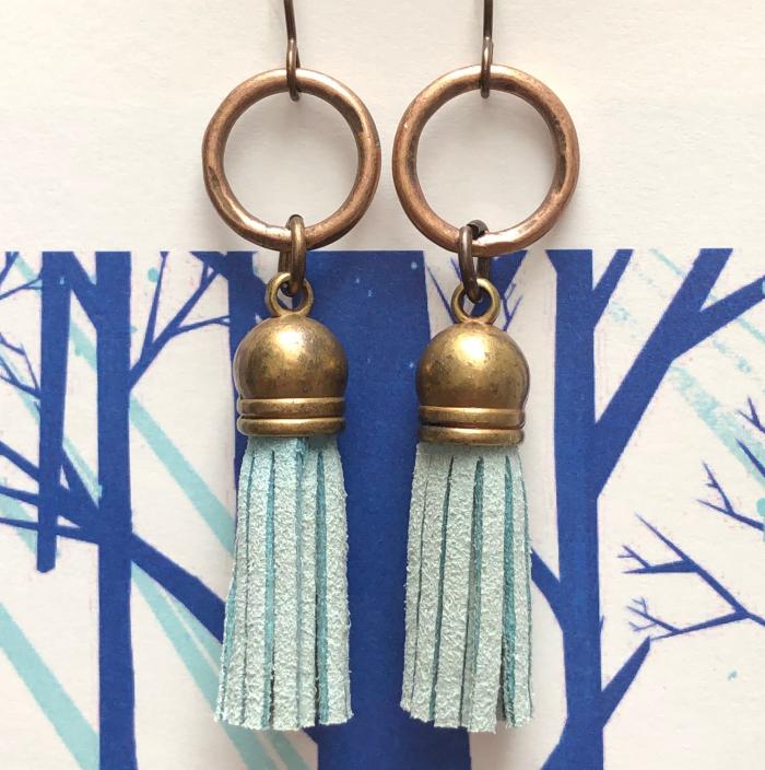 Boucles d'oreilles composées de pompons en suédine bleue et d'anneaux en laiton. Crochets d'oreilles en laiton.