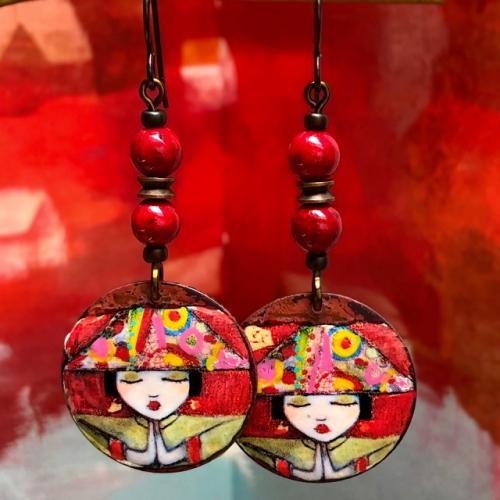 Boucles d'oreilles composées de pendentifs artisanaux en cuivre émaillé et de perles rouges en howlite. Crochets d'oreilles en niobium. Pièces uniques.