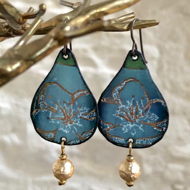 Boucles d'oreilles composées de pendentifs artisanaux en cuivre émaillé bleus et de perles en métal doré. Crochets d'oreilles en laiton. Pièces uniques.