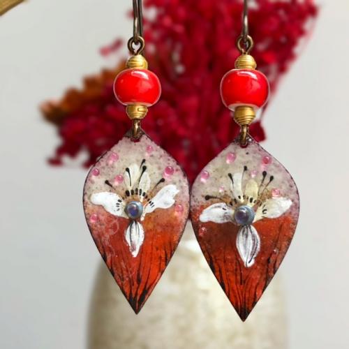 Boucles d'oreilles composées de pendentifs artisanaux en cuivre émaillé et de perles africaines. Crochets d'oreilles en laiton. Pièces uniques.