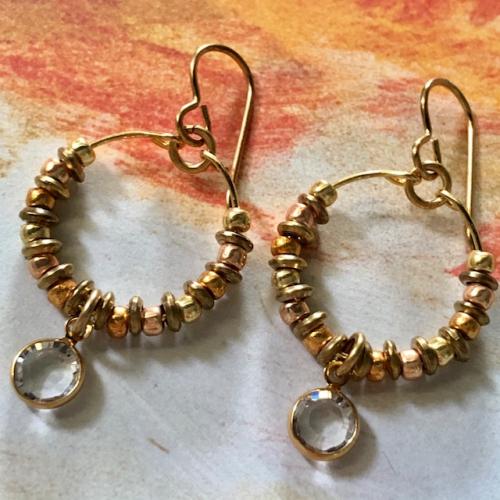 Créoles composées d'une breloque en cristal Swarovski, de perles de rocailles japonaises Toho et de perles en laiton. Crochets d'oreilles en métal.