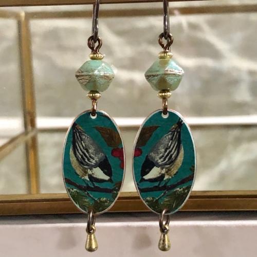 Boucles d'oreilles composées de pendentifs artisanaux en cuivre illustré et de perles en vert tchèque. Crochets d'oreilles en laiton. Pièces uniques.