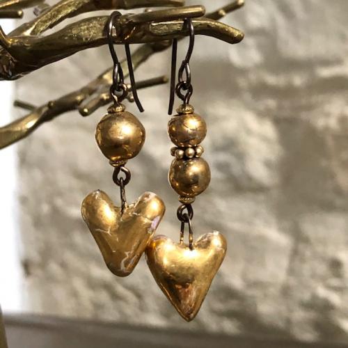 Boucles d'oreilles asymétriques composées de pendentifs artisanaux en céramique or et de perles en laiton. Crochets d'oreilles en laiton. Pièces uniques.