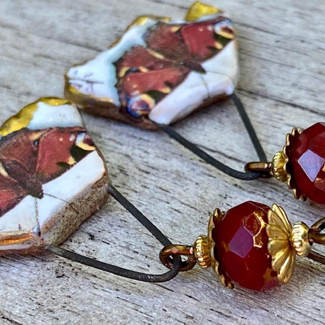 Boucles d'oreilles composées de pendentifs artisanaux en céramique et de perles rouge en verre tchèque. Crochets d'oreilles en laiton. Pièces uniques.