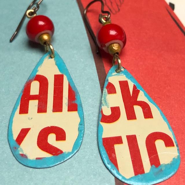 Boucles d'oreilles composées de pendentifs en métal illustré et d'anciennes perles africaines. Crochets d'oreilles en laiton. Pièces uniques.