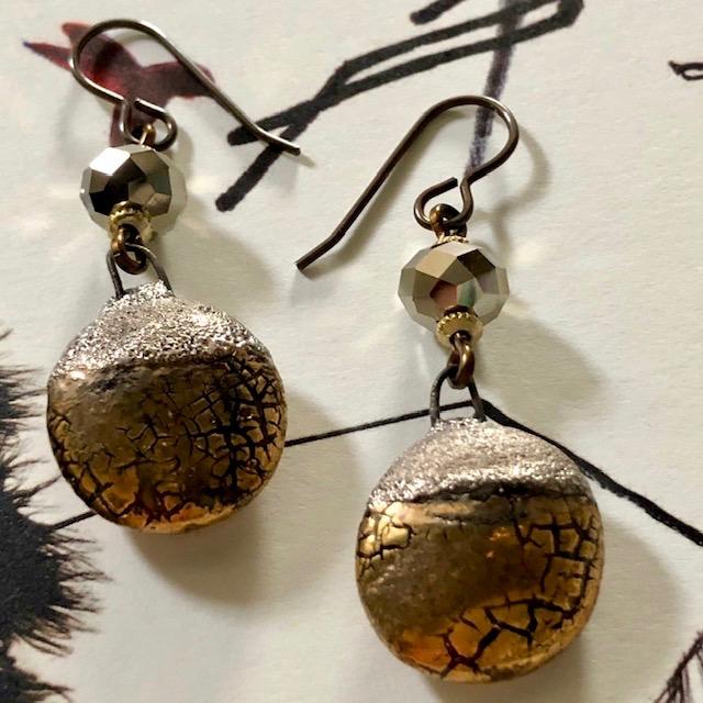 Boucles d'oreilles composées de pendentifs artisanaux en céramique or et de perles facettées en cristal Swarovski. Crochets d'oreilles en laiton.