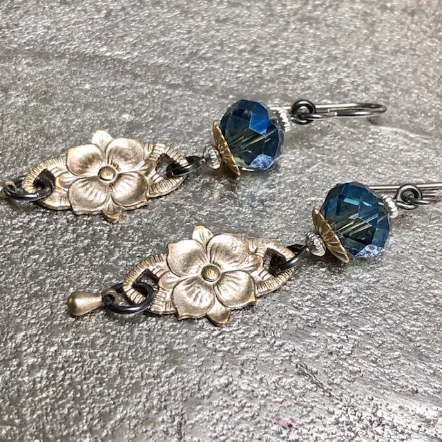 Boucles d'oreilles composées de jolies perles en cristal bleues et de fleurs en laiton argentées. Crochets d'oreilles en niobium.