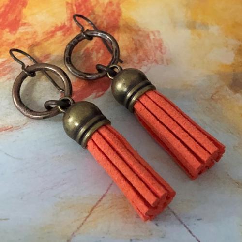 Boucles d'oreilles composées de pompons en suédine orange et surmontées d'anneaux en laiton. Crochets d'oreilles en laiton.