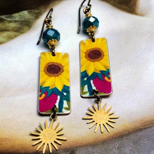Boucles d'oreilles composées de pendentifs artisanaux en cuivre illustré et de perles en apatite bleues. Crochets d'oreilles en laiton. Pièces uniques.