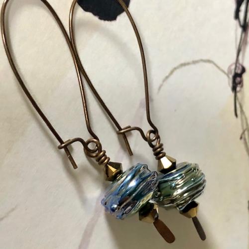 Boucles d'oreilles composées de perles artisanales en verre filé au chalumeau bleu-verre et de perles en cristal Swarovski. Crochets d'oreilles en laiton.