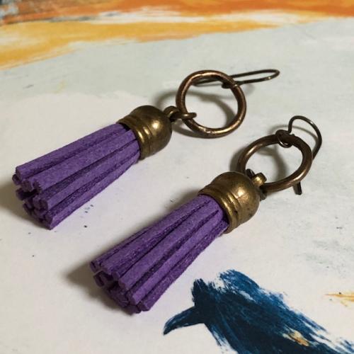 Boucles d'oreilles composées de pompons en suédine et surmontées d'anneaux en laiton. Crochets d'oreilles en laiton.