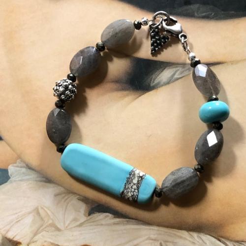 Bracelet composé de perles lampwork, de perles facettées en labradorite et de perles en argent Thaï Karen. Fermoir en argent. Pièce unique.