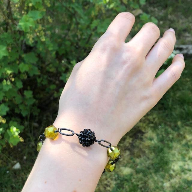 Bracelet composé de perles en verre tchèque et d'une perle noire en plasticine ornée de strass. Chaîne et fermoir en laiton. Pièce unique.