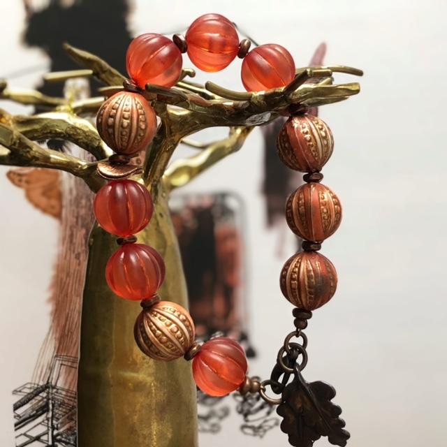 Bracelet composé de jolies perles en acrylique rose cuivré, orange brûlée et de différentes perles en cuivre. Pièce unique.