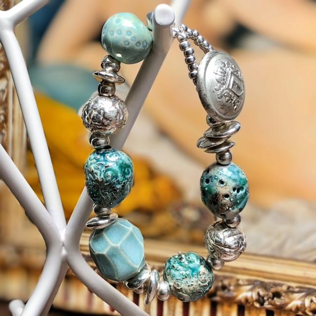 Bracelet composé de perles artisanales en céramique bleu-vert et argentées et de perles de rocaille. Pièce unique.