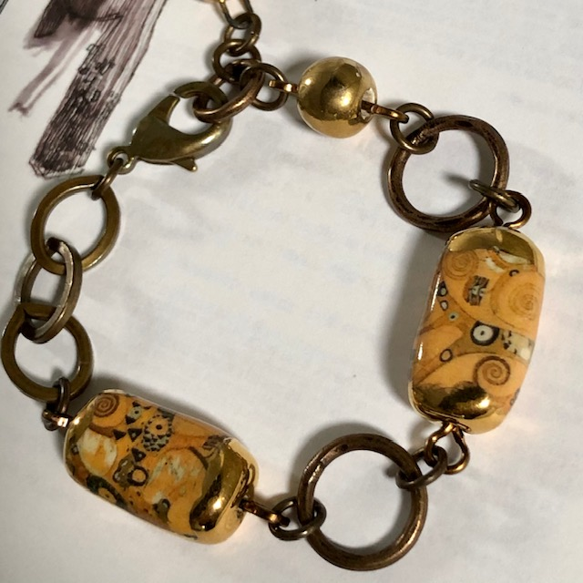 Bracelet composé de perles artisanales en céramique figurant L'Arbre de Vie de Klimt. Anneaux et chaîne en laiton. Pièce unique.