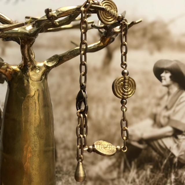 Bracelet composé de superbes perles africaines, d'une chaîne artisanale en laiton et d'une jolie breloque. Bracelet réglable.