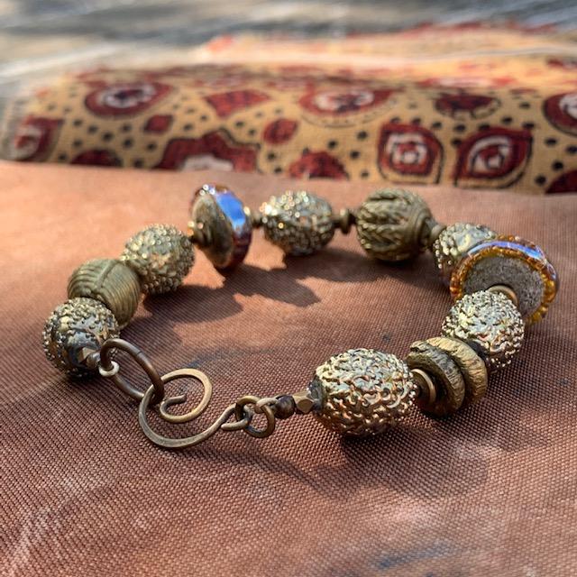 Bracelet aux couleurs du désert composé de perles Lampwork et de perles africaines en laiton. Fermoir en laiton. Pièce unique.