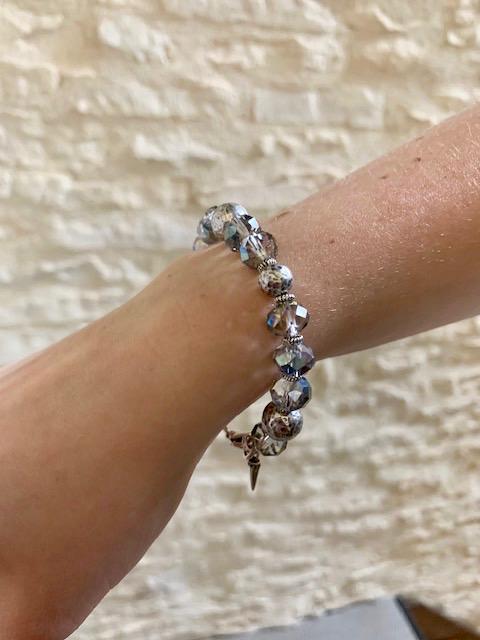 Bracelet composé de perles facettées en cristal et de perles en métal argenté. Fermoir et breloques en argent.