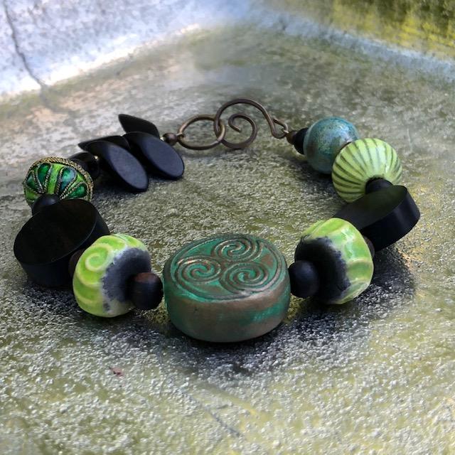 Bracelet composé de perles artisanales en céramique, de perles en bois d'ébène et de perles en cuivre émaillé. Fermoir en laiton. Pièce unique.