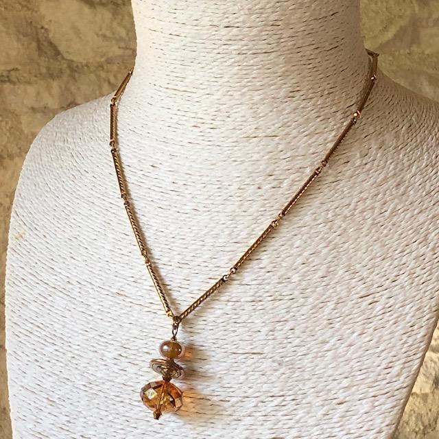 Collier composé d'une belle perle facettée en cristal Swarovski et de perles Lampwork. Chaîne en métal doré. Pièce unique.