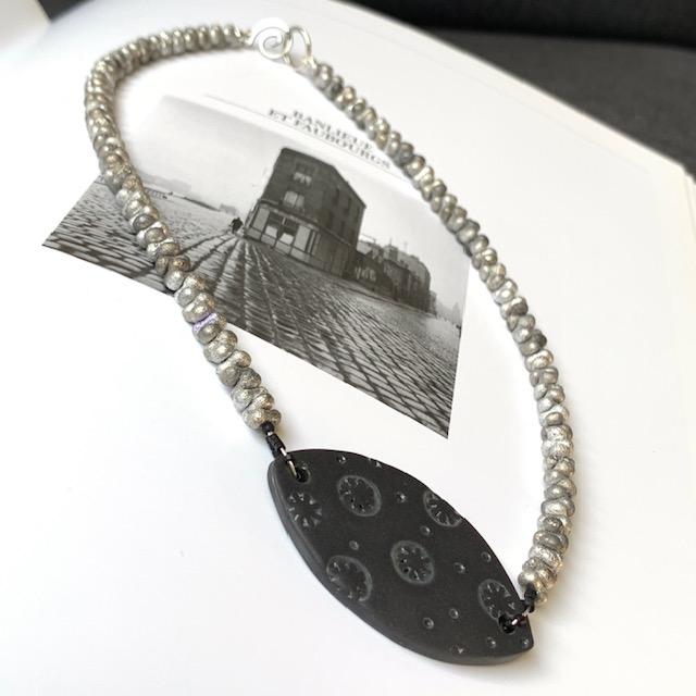 Collier (ras-de-cou) composé d'un pendentif artisanal en céramique et de perles Farfalle en verre tchèque. Pièce unique.