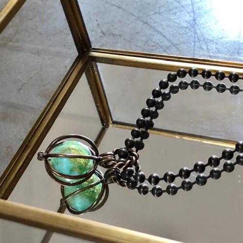 Collier composé d'un pendentif cage en laiton et d'une perle de Murano. Chaîne en laiton. Pièce unique.