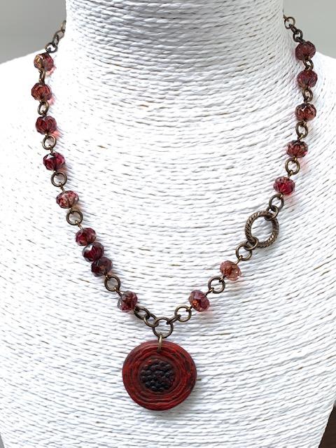 Collier composé d'un pendentif artisanal en pâte polymère et de perles en verre de Bohême. Chaîne et fermoir en laiton. Pièce unique.