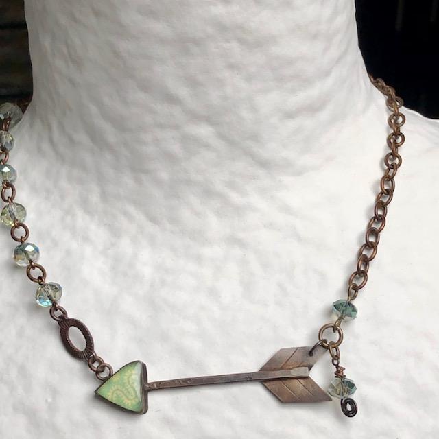 Collier (ras-du-cou) composé d'un pendentif artisanal en résine, de perles en verre tchèque vert pâle et d'un connecteur en métal cuivré. Pièce unique.