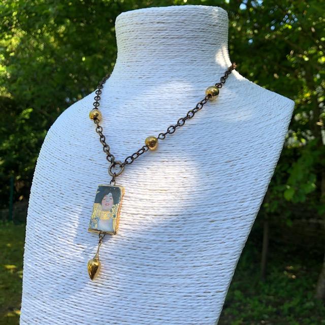 Collier composé d'un pendentif artisanal en céramique représentant Judith de Klimt et de perles dorées en céramique. Chaîne en laiton. Pièce unique.