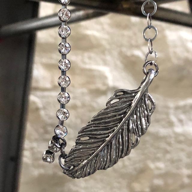 Collier composé d'un pendentif artisanal en étain et de deux chaînes, l''une incrustée de cristaux Swarovski et l'autre en Argent vieilli. Pièce unique.