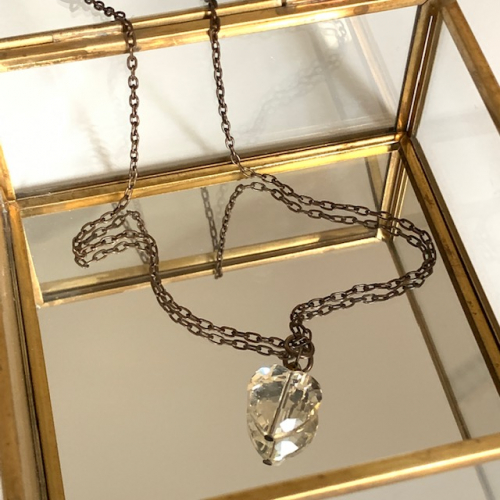 Collier composé d'un coeur facetté en cristal couleur citrine et d'une perle en cristal Swarovski chocolat. Chaîne en laiton.