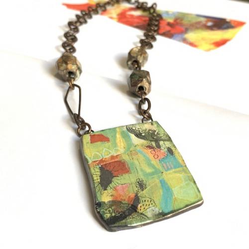 collier composé d'un magnifique pendentif artisanal et de perles facettées en céramique. Chaîne et fermoir en laiton